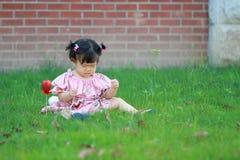 Behandla som ett barn flickalek på gräsmattan som är olycklig, miss hennes moder Royaltyfria Bilder