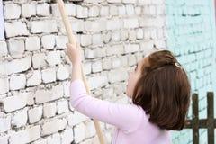 Behandla som ett barn flickamålarfärger väggarna med rullen och målarfärg arkivfoton