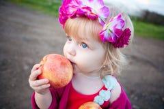 Behandla som ett barn flickan äter ett äpple Royaltyfri Foto