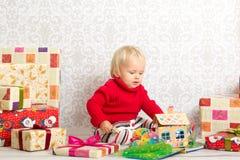 Behandla som ett barn flickan bland julgåvorna Arkivbild