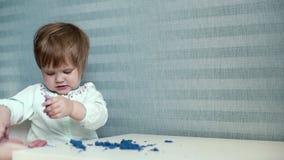 Behandla som ett barn flickan dumpar kinetisk sand från tabellen till golvet i ultrarapid stock video