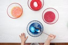 Behandla som ett barn flickan som förbereder påskägg Arkivfoton