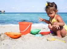 Behandla som ett barn flickan har gyckel på stranden Royaltyfri Foto