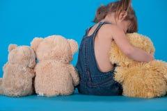 behandla som ett barn flickan henne som kramar toys Arkivfoton