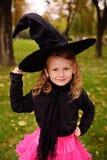Behandla som ett barn flickan i en karnevaldräkt och en hatt för häxa` s på en allhelgonaafton royaltyfri fotografi