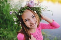 Behandla som ett barn flickan i en krans av vildblommor Arkivbild