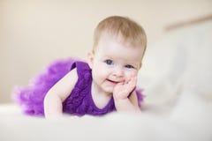 Behandla som ett barn flickan i en purpurfärgad klänning som ligger på sängen Royaltyfri Foto