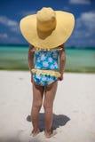 Behandla som ett barn flickan i hennes solhatt på stranden Royaltyfria Foton