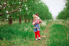 Behandla som ett barn flickan i maskrosor för blomningvårträdgårdar Arkivbild