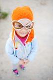 Behandla som ett barn flickan i pilot- hatt som ler på kameran Royaltyfri Fotografi