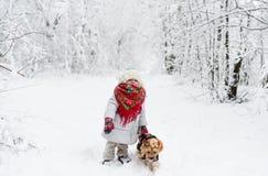 Behandla som ett barn flickan i röd halsduk med den lilla hunden i en vinterskog royaltyfri bild