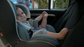 Behandla som ett barn flickan i ett säkerhetsbilsäte Säkerhet och trygghet stock video
