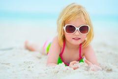 Behandla som ett barn flickan i solglasögon som lägger på stranden Royaltyfria Bilder