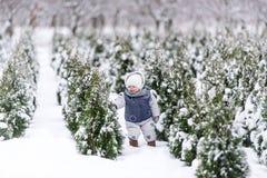 Behandla som ett barn flickan i varm snowsuit som går i vintern, parkerar med en vit snö Royaltyfri Fotografi