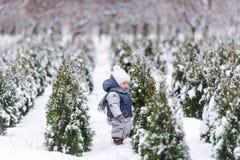 Behandla som ett barn flickan i varm snowsuit som går i vintern, parkerar med en vit snö Arkivfoto
