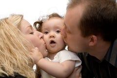 behandla som ett barn flickan isolerade kyssande föräldrar arkivfoton