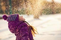 Behandla som ett barn flickan kastar den insnöade frostiga vintern parkerar Flygsnöflingor solig dag Barn som har roligt utomhus arkivbild