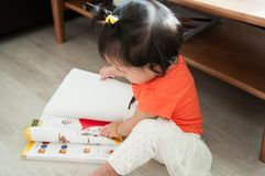 Behandla som ett barn flickan läser en bok arkivfoton
