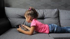 Behandla som ett barn flickan som ligger på soffan med minnestavlan Liggande spela för liten flicka på minnestavlan lager videofilmer