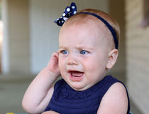 Behandla som ett barn flickan med öraknip Arkivfoto