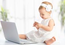 Behandla som ett barn flickan med bärbar dator- och kreditkortshopping på internet Arkivfoton