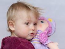 Behandla som ett barn flickan med dockan Arkivfoto