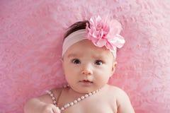 Behandla som ett barn flickan med en stor, rosa, blommahuvudbindel och pärlor Arkivfoto