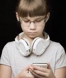 Behandla som ett barn flickan med hörlurar och telefonen på mörk bakgrund Royaltyfria Bilder