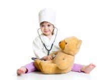 Behandla som ett barn flickan med kläder av doktorn som spelar med leksaken Arkivfoton