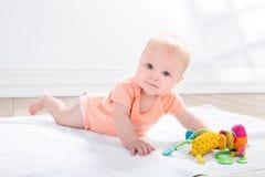 Behandla som ett barn flickan med leksaken som ligger på golvet Royaltyfri Fotografi