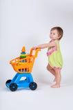 Behandla som ett barn flickan med leksakshoppingvagnen bakgrund isolerad white royaltyfri fotografi