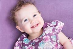 Behandla som ett barn flickan med lockigt hår som bär en purpurfärgad klänning Royaltyfri Foto