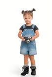 Behandla som ett barn flickan med tappningkameran som poserar i studio isolerat Royaltyfri Foto