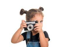 Behandla som ett barn flickan med tappningkameran som poserar i studio isolerat Arkivbild