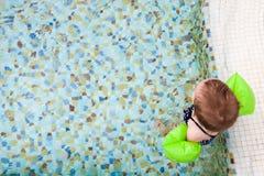 Behandla som ett barn flickan med uppblåsbara armbindlar Barn som lär att simma i pöl royaltyfri fotografi