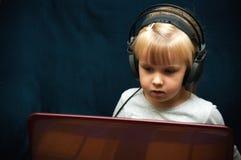Behandla som ett barn flickan och bärbara datorn Royaltyfri Foto