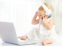 Behandla som ett barn flickan på bärbar datordatoren, mobiltelefon Royaltyfri Bild