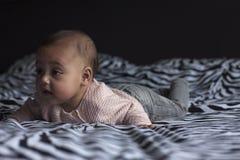Behandla som ett barn flickan på buken i säng royaltyfri foto