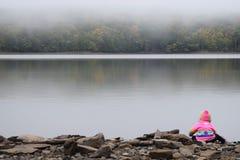 Behandla som ett barn flickan på den dimmiga sjön Arkivfoto