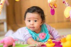 Behandla som ett barn flickan på golv med leksaker Royaltyfria Bilder