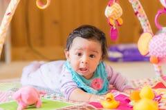 Behandla som ett barn flickan på golv med leksaker Royaltyfri Foto