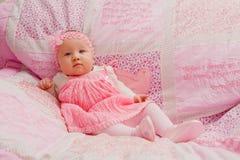 Behandla som ett barn flickan på rosa färgfilten Royaltyfri Fotografi