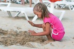 Behandla som ett barn flickan på stranden. Arkivfoton