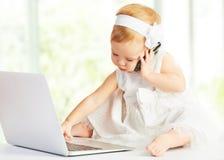 Behandla som ett barn flickan på bärbar datordatoren, mobiltelefon Royaltyfri Foto