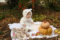 Behandla som ett barn flickan som poserar med pumpa och leksaker bland träd i höstmedeltal Royaltyfria Bilder