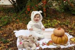 Behandla som ett barn flickan som poserar med pumpa och leksaker bland träd i höstmedeltal Royaltyfria Foton