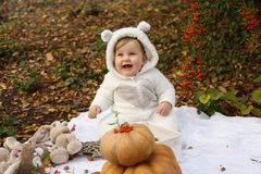 Behandla som ett barn flickan som poserar med pumpa och leksaker bland träd i höstmedeltal Arkivfoto
