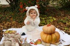 Behandla som ett barn flickan som poserar med pumpa och leksaker bland träd i höstmedeltal Arkivfoton