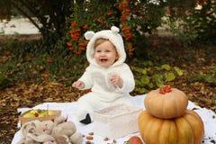 Behandla som ett barn flickan som poserar med pumpa och leksaker bland träd i höstmedeltal Arkivbilder