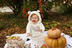 Behandla som ett barn flickan som poserar med pumpa och leksaker bland träd i höstmedeltal Fotografering för Bildbyråer